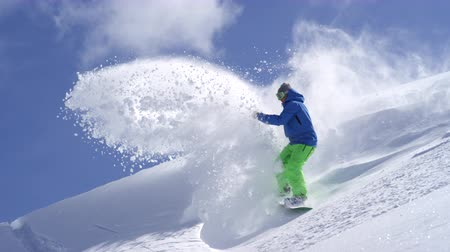 into the camera : SLOW MOTION CLOSE UP: Extreme snowboarder riding powder and doing powder turns, spraying snow in sunny mountain backcountry. Snowboarder having fun snowboarding in fresh snow off piste