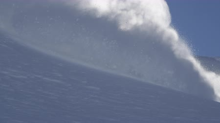 into the camera : SLOW MOTION CLOSE UP: Extreme snowboarder riding powder and doing powder turns, spraying snow over sun in sunny mountain backcountry. Snowboarder having fun snowboarding in fresh snow off piste Stock Footage