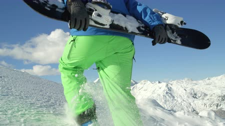 freeride : SLOW MOTION CLOSE UP: Extreme snowboarder hiking uphill in fresh powder snow towards mountain summit in winter. Freeride snowboarder climbing to the mountaintop in backcountry mountain ski resort Stock Footage