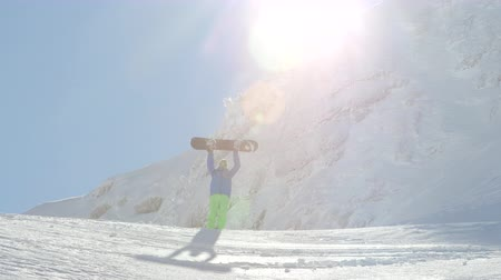 freeride : Extreme snowboarder hiking uphill, reaching mountain summit and raising snowboard proudly. Freeride snowboarder reaching snowy mountaintop, raising his snowboard successfully in mountain ski resort