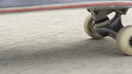 skateboard deck : SLOW MOTION CLOSE UP MACRO: Unrecognizable skateboarder skateboarding along the concrete street on a sunny summer day. Extreme closeup of a skateboard deck and wheels spinning on a pavement Stock Footage