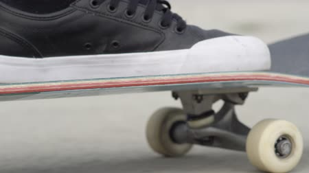 skateboard deck : SLOW MOTION CLOSE UP: Unrecognizable skateboarder skateboarding along the street on sunny day. Extreme closeup of skateboarders legs and sneakers standing and pushing skate deck with wheels spinning