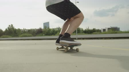 skateboard deck : SLOW MOTION CLOSE UP: Unrecognizable skateboarder skateboarding and jumping ollie tricks on street. Extreme closeup of skateboarders legs and sneakers jumping flip trick with skateboard outdoors.