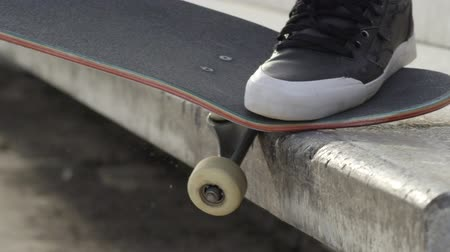 skateboard deck : SLOW MOTION EXTREME CLOSE UP DOF: Unrecognizable skateboarder jumping and sliding on concrete bench on street. Closeup of skaters legs skateboarding and doing grinding trick with skateboard in a city