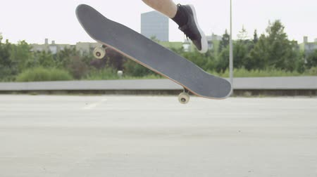 skateboard deck : SLOW MOTION CLOSE UP DOF: Unrecognizable skateboarder skateboarding and jumping ollie flip trick on concrete street in sunny summer. Skateboarder jumping kickflip trick with skateboard in the city