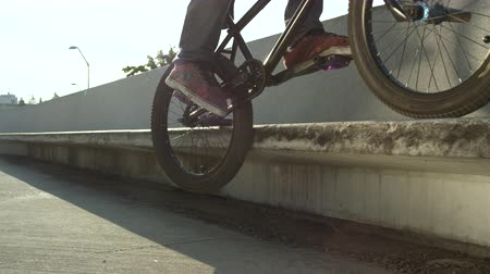 construir : SLOW MOTION CLOSE UP DOF: Extreme bmx biker jumping on a concrete bench in park and sliding the edge on sunny day. Sun shining through cool biker jumping and doing peg grind tricks in summer