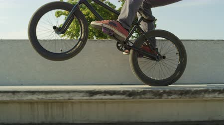 construir : SLOW MOTION CLOSE UP DOF: Extreme bmx biker jumping on a concrete bench in park and riding on back wheel on sunny day. Unrecognizable cool biker jumping and doing wheelie trick on beautiful summer day