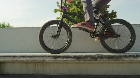 construir : SLOW MOTION CLOSE UP DOF: Extreme bmx biker jumping on a concrete bench in park and riding on sunny day. Unrecognizable cool biker jumping and doing tricks on beautiful summer day Stock Footage