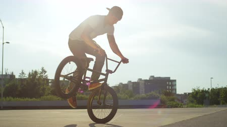 кнут : SLOW MOTION CLOSE UP: Extreme bmx biker riding in sunny park, stopping the bmx bike and doing nollie tail whip trick on beautiful summer day. Cool young bmx biker performing tricks on city street