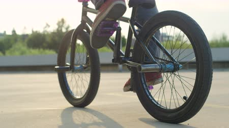 spor ayakkabısı : SLOW MOTION CLOSE UP: Unrecognizable extreme bmx biker pedaling and riding bike in sunny park in beautiful summer. Cool young bmx biker doing tricks over the sunset sun in city park on sunny day Stok Video