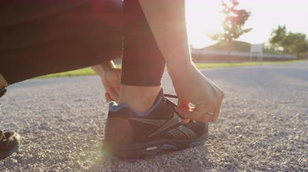 raios de sol : SLOW MOTION, CLOSE UP, DOF: Energetic active young woman in good shape lacing her running shoes to start jogging in local park on amazing sunny summer day. Healthy girl living an active way of life Stock Footage