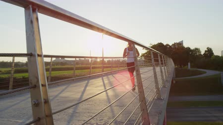 speedway : SLOW MOTION CLOSE UP: Female running in green park in small suburban town with tall buildings in the background. Girl jogging across steel bridge leading above heavy traffic highway at golden sunset Stock Footage