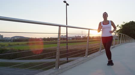 pista de corrida : SLOW MOTION CLOSE UP: Female running in green park in small suburban town with tall buildings in the background. Girl jogging across steel bridge leading above heavy traffic highway at golden sunset Vídeos