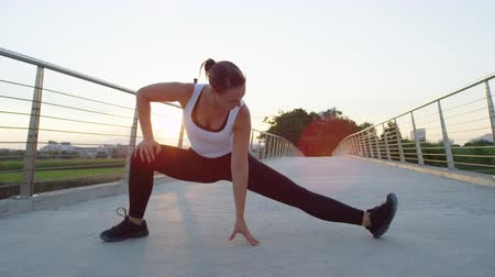 пригород : SLOW MOTION, CLOSE UP: Healthy fit young girl doing cool down on bridge, making adductor stretch after long and challenging running session in green city park at beautiful sunny morning at sunrise Стоковые видеозаписи