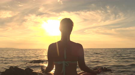 pozisyon : CLOSE UP: Tranquil girl sitting on rock by rippling sea, meditating in lotus yoga pose, concentrating, observing breath and relaxing mind, soul and body under fiery glowing sun and golden setting sky Stok Video