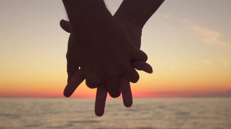 parceiro : SLOW MOTION, CLOSE UP: Affectionate boyfriend and romantic girlfriend holding hands tightly fingers crossed, showing love, care and intimate friendship to each other at dreamy ocean shore at sunset