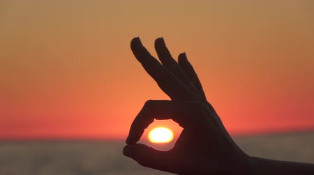 superb : SLOW MOTION, CLOSE UP, DOF: Connecting thumb and index finger, showing diving signal OK, all is well, good or the food is well. Woman making nonverbal communication signs and symbols at magical sunset