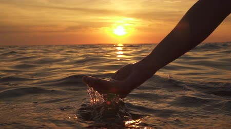 waterdrop : SLOW MOTION, CLOSE UP, DOF: Woman scooping smooth salty water into her hands and dropping it, waterdrops splashing, hitting glossy sea surface. Young girl playing in ocean at dreamy golden sunset