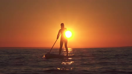 sup : SLOW MOTION CLOSE UP: Active sporty girl standing on inflatable SUP and paddling at amazing golden sunset, admiring beautiful beach. Woman propelling herself slowly through the water using paddle Stock Footage