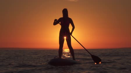 sup : SLOW MOTION CLOSE UP: Active sporty girl standing on inflatable SUP, paddling at amazing golden sunset, admiring beautiful beach and relaxing. Woman standup paddleboarding in splashing rippling sea