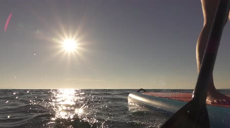 sup : SLOW MOTION, CLOSE UP: Woman standing firmly on inflatable SUP board and paddling. Hands pushing and pulling the paddle through the water and propelling paddleboard at breathtaking sunny summer day Stock Footage