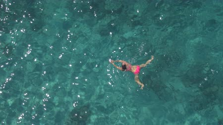 penetrating : AERIAL, CLOSE UP: Attractive Caucasian girl swimming and looking around in beautiful turquoise crystal clear ocean. Sunshine penetrating sparkling water revealing stunning rocky and sandy sea bottom