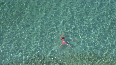žába : AERIAL, CLOSE UP: Pretty Caucasian girl swimming basic breaststroke technique in beautiful turquoise crystal clear ocean. Sunshine penetrating sparkling water revealing rocky and sandy sea bottom