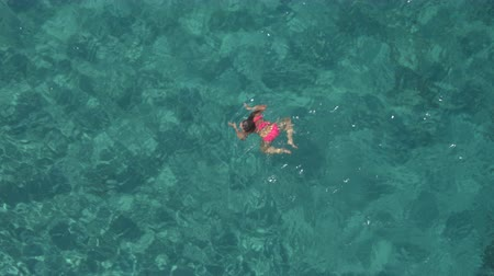 penetrating : AERIAL: Attractive young woman coming for air, submerging and swimming underwater in crystal clear transparent turquoise ocean. Sunlight penetrating water surface revealing stones, sand on sea bottom Stock Footage
