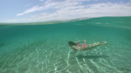 odrážející : SLOW MOTION, CLOSE UP, UNDERWATER: Attractive young brunette girl diving underwater in crystal clear ocean lagoon. Sun rays penetrating water surface and reflecting on stunning white sandy sea bottom