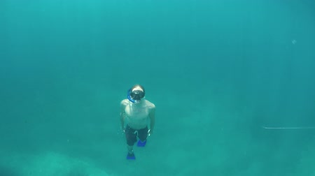 coming : SLOW MOTION CLOSE UP UNDERWATER: Athletic young guy diving in deep blue ocean with amazing rocky seabed, swimming to the surface for air. Sunshine penetrating transparent water on sunny summer day