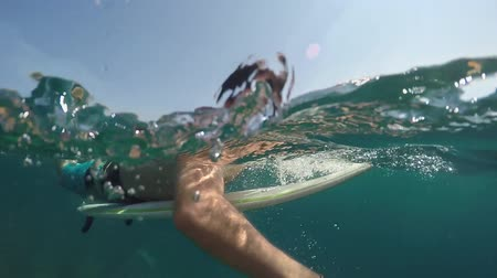 extreme close up : SLOW MOTION HALF UNDERWATER: Young man paddling out on surfboard in open water ocean. Cheerful male surfer smiling and paddling to lineup in crystal clear blue sea on summer vacations at the seaside