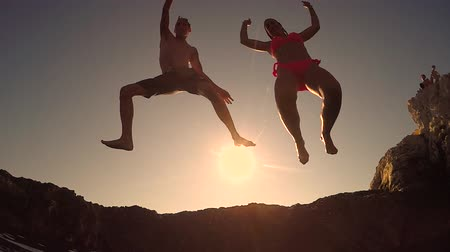 pinky : SLOW MOTION CLOSE UP LOW ANGLE VIEW: Two happy playful friends jumping off sharp rocky ledge into stunning ocean with hands raised at magical pinky summer sunset. Water drops splashing and sprinkling