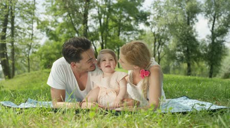 pinky : SLOW MOTION CLOSE UP DOF: Happy young mum and dad lying on the grass in park on beautiful day and caressing cheerful sweet baby girl in pinky dress. Idyllic family video calling and waving into camera