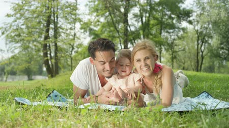 pinky : SLOW MOTION CLOSE UP DOF: Cute happy young dad and pretty blonde mum lying on blanket on grass in park. Cheerful sweet baby girl in pinky dress clapping with her feet and smiling on perfect summer day Stock Footage