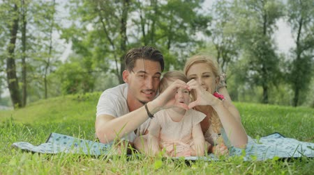pinky : SLOW MOTION, CLOSE UP, DOF: Loving young parents lying on blanket on meadow field in green park, making heart-shaped symbol with their hands. Smiling baby girl in pinky dress enjoying sunny spring day