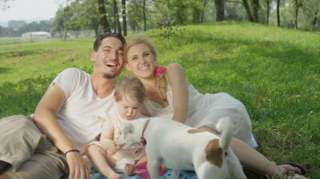 szülő : SLOW MOTION, CLOSE UP, DOF: Perfect young family spending quality time in park. Smiling baby girl eating biscuits, cute dog stealing them. Beautiful mother and cheerful father watching and laughing