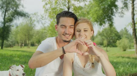 em forma de : SLOW MOTION, CLOSE UP, DOF: Beautiful blonde Caucasian woman and dark haired man sitting together on soft blanket in lush Central park and making heart shaped sign with fingers. Perfect couple in love Stock Footage