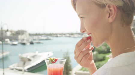 정박 : SLOW MOTION CLOSE UP DOF: Cheerful adult Caucasian woman on vacation eating sweet strawberry and drinking cocktail on hotel terrace, enjoying the view of sailboat harbor on amazing sunny summer day