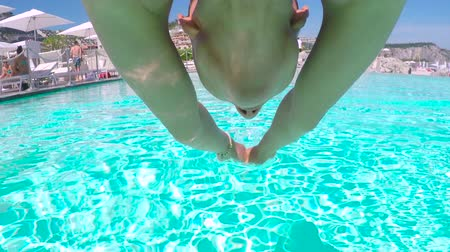 ожерелье : POV, LOW ANGLE VIEW, UNDERWATER: Happy young Caucasian girl jumping head first into outdoor swimming pool and diving deep. Woman coming to the surface to catch a breath, wiping water off her face Стоковые видеозаписи