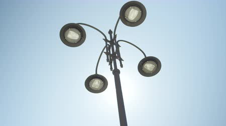 sokak lâmbası direği : SLOW MOTION, CLOSE UP, LOW ANGLE: Interesting steel street lamps facing downwards, decorated with tendrils, patterns and shapes in modern architectural design. Green and energy saving LED streetlight