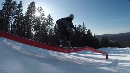 snowboarder : SLOW MOTION, CLOSE UP, FOLLOW: Extreme snowboarder riding rails and doing tricks. Boarder jumping on kink rail and sliding down. Stock Footage