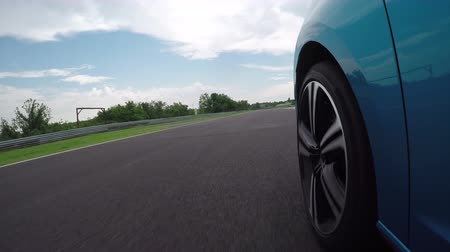 závodní dráha : CLOSE UP, LOW ANGLE VIEW: Blue personal car driving practice qualifying lap on luxury Hungaroring racing track and chasing other car at the ring. Racecar competing on professional racetrack circuit