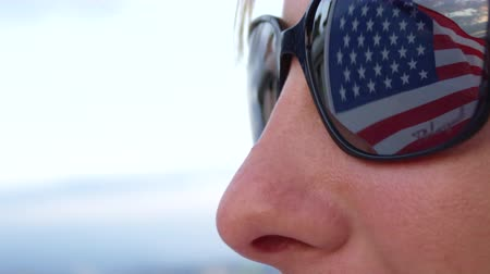 homeland : CLOSE UP, SLOW MOTION: Colorful American flag waving in the wind and reflecting in young womans sunglasses. Proud American citizen and patriot supporting political party, nation, culture and freedom