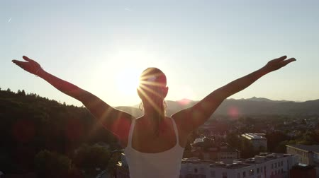 kabarık : SLOW MOTION, CLOSE UP: Pretty woman illuminated by the sun standing on the top of skyscraper, looking down on buildings and people raising hands, feeling powerful and in control like almighty God