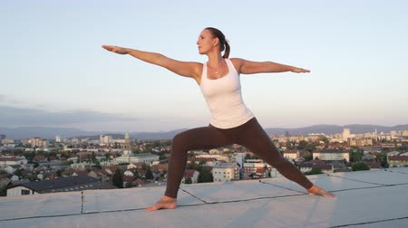 legginsy : SLOW MOTION, CLOSE UP: Young woman doing warrior pose right foot bent standing on edge on top of skyscraper above big urban town with overgrown hills and mountains in the background at golden sunrise