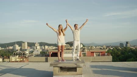tetőtéri : SLOW MOTION CLOSE UP: Excited girl and smiling boy holding hands and raising them in the air on the rooftop above urban city illuminated by rising sun. Happy couple celebrating success and loving life