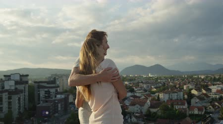 iluminado pelo sol : SLOW MOTION CLOSE UP: Happy boyfriend and smiling girlfriend standing embraced on edge of tall skyscraper looking down on beautiful city, colorful houses and rooftops illuminated by the morning sun Stock Footage