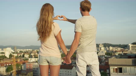 em forma de : SLOW MOTION CLOSE UP, DOF: Beautiful girl with long hair and attractive boyfriend standing on the edge of skyscraper rooftop, holding hands and making heart shaped symbol with fingers at sunny evening
