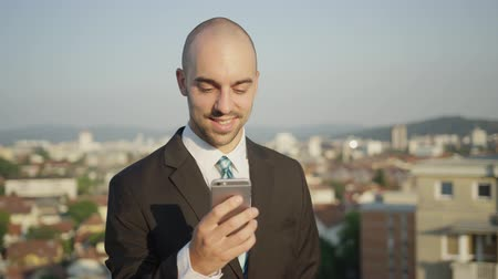 correspondência : SLOW MOTION, CLOSE UP, DOF: Young successful businessman standing on rooftop with beautiful view of urban city in the background and working outdoors on smartphone, texting messages and writing emails