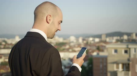 correspondência : SLOW MOTION, CLOSE UP, DOF: Successful smiling entrepreneur working on mobile phone writing messages to business colleagues. Man standing on the rooftop above colorful city at amazing sunny summer day